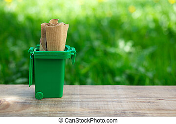 separating old paper in green container to save natural resources