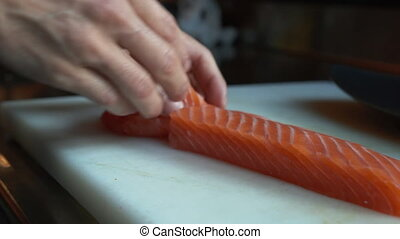 Separating sliced pieces of salmon from the rest. Cook in protective gloves preparing red fish for serving