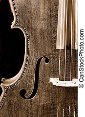 Sepia closeup of a cello on a black background