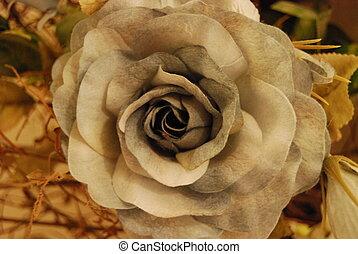 a close up of a blue-gray felt rose with a brown material background set in sepia tones