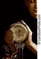 Sepia picture of a beautiful girl with a clock (focus on clock)