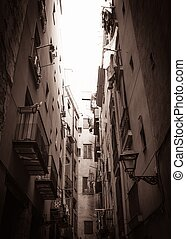 Sepia picture of narrow street end with balconies