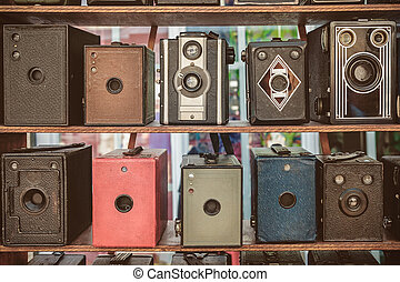 Sepia toned image of old box cameras on a flee market in...