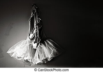 sepia toned image of tutu and ballet slippers hanging on wall lit from sunlight on the left with plenty of space for copy or text.