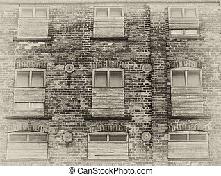 sepia view of an old abandoned commercial warehouse building with weathered brick walls and boarded up windows