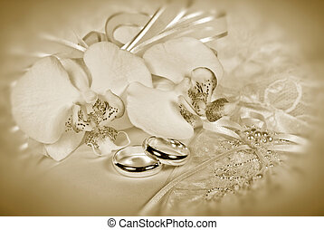 Orchid bridal bouquet with wedding rings in sepia tones.