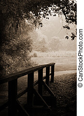 Sepia wooden bridge - A small wooden footbridge leads out of...