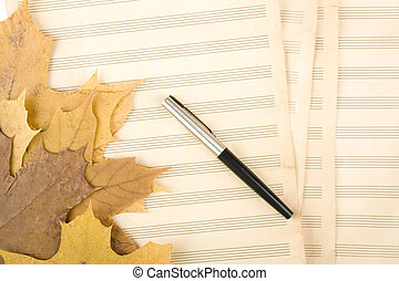 Old sheet music sheet of paper which has a handle and the autumn leaves of maple