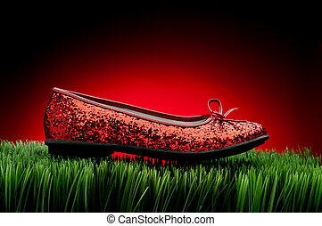 Sequined red slipper on green grass against a fading red...