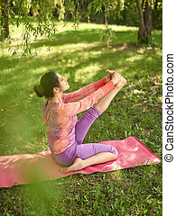 Serene and peaceful woman practicing mindful awareness mindfulness by meditating in nature at sunset