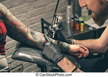 Serene bearded man creating tattoo on hand