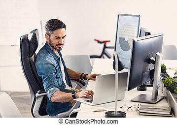 Serene bearded man working on laptop