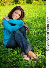 Serene beautiful woman resting on green grass