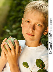 Serene blond and blue eyed boy holds green ball