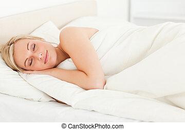 Serene blonde woman sleeping in her bedroom
