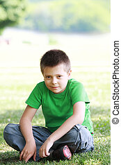 Serene boy in casual on grass