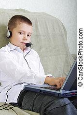 Serene boy in headset working on laptop