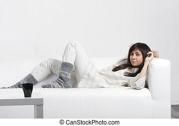 Serene brunette laying down on sofa