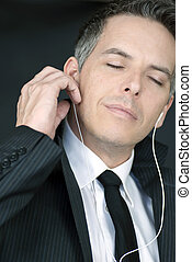 Serene Businessman Puts In Headphones