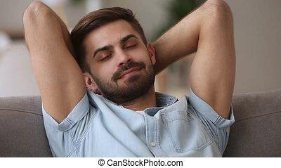 Serene calm man relaxing on sofa enjoying comfort peaceful...