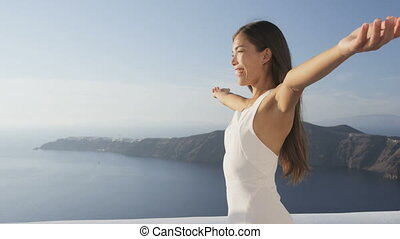Serene cheerful happy Asian woman standing with arms outstretched. Carefree female is against sea and mountains. Attractive lady in white sundress is enjoying summer vacation. Santorini, Greece.