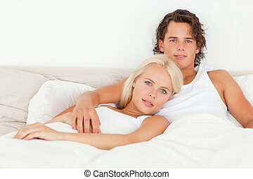 Serene couple lying on a bed