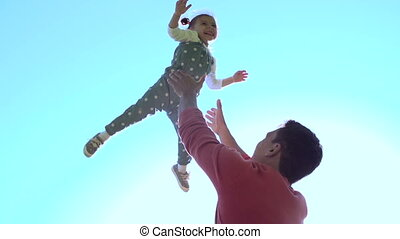Serene Family - Slow motion of handsome father throwing his...