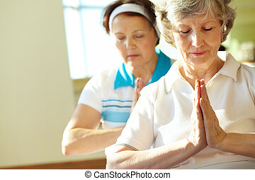 Serene females - Portrait of two aged females doing yoga ...