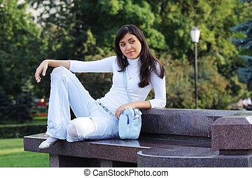 Serene girl on stone bench