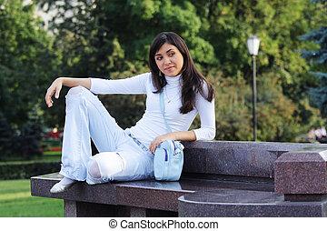 Serene girl on stone bench