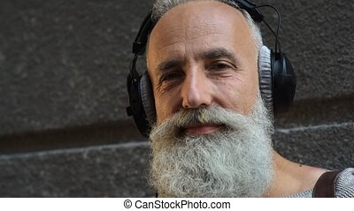 Serene greyhaired guy putting off his headphones outdoors