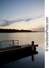Serene harbour with dock at sunset
