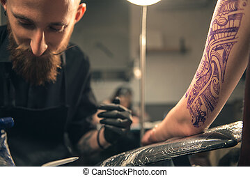 Serene male doing tattoo on arm