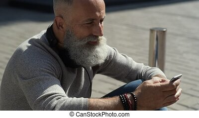 Serene mature guy in casual using smartphone outdoors -...
