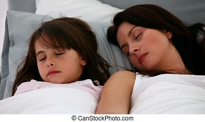 Serene mother and daughter sleeping together on a bed