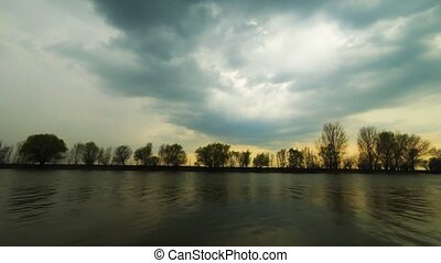 Serene savage scene. A light wind ruffled the water and stormy clouds fly away over the trees on riverbank. Sundown.