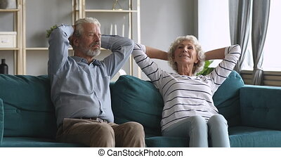Serene senior older couple relaxing on comfortable sofa together