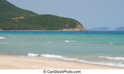Serene view of sandy beach, sea with small waves and woody mountain on horizon