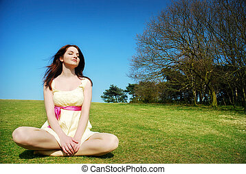 Serene woman in field - A beautiful young serene woman...