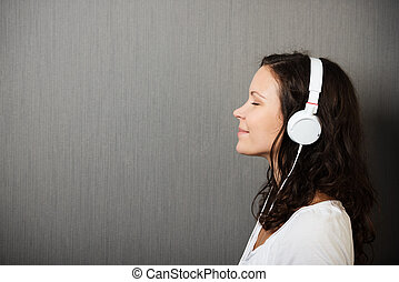 Serene young woman enjoying her music standing in profile...