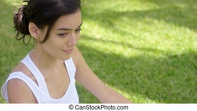 Serene young woman meditating on a green lawn with her eyes...