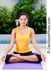 Serene young woman sitting in lotus position outdoors -...
