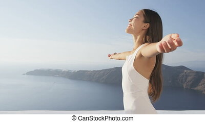 Serenity free carefree young woman standing with arms outstretched relaxing in enjoying freedom. Happy girl on Santorini, Greece. Attractive lady in white sundress on summer vacation travel RED EPIC.
