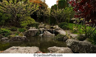 Serenity In Japan Garden, Pond Bordering By Boulders and...