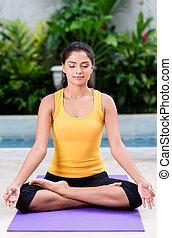 sereno, mujer joven, sentar posición lotus, aire libre