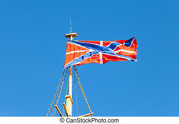 Serf Russian Navy flag on the flagpole against blue sky