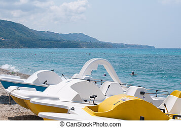 Series of boats with a slide on the beach waiting to sail