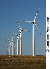 Series of wind power generators in a grass field