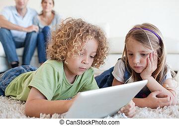 serieuze , kinderen, gebruik, een, tablet, computer, terwijl, hun, vrolijke , ouders, zijn, schouwend, in, hun, woonkamer