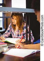 serieuze , student, zitting op het bureau, schrijvende , in, notepad